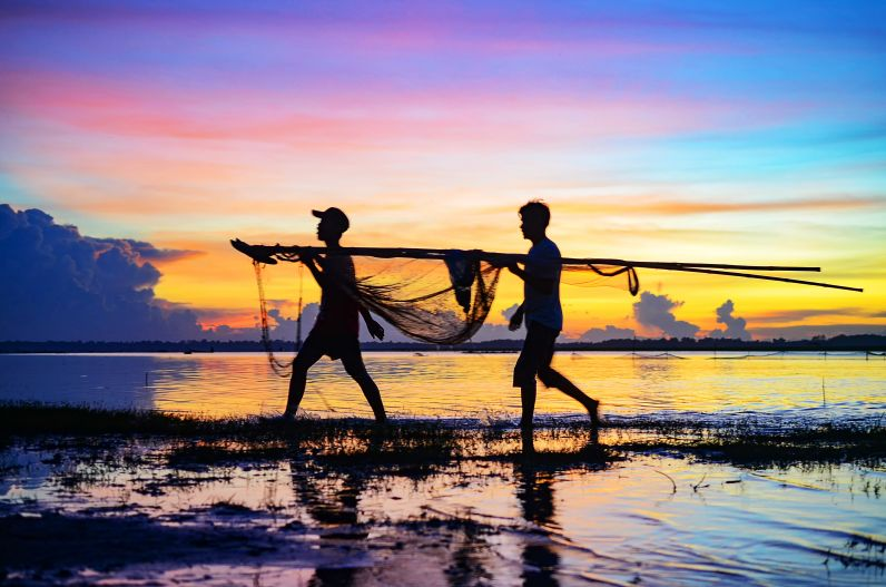 Men working at sunset on Mekong in Prey Veng, Cambodia.