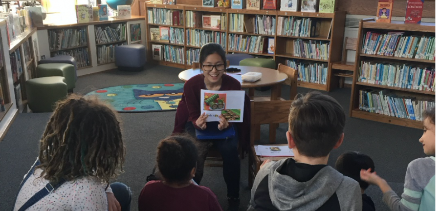 Volunteer reading book to students